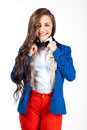 Young woman in red pants and blue coat smiling on camera Royalty Free Stock Photo