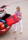 Young woman with a red suitcase in the car Stock Photography