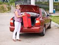 Young woman with a red suitcase in the car puts trunk of Stock Photography