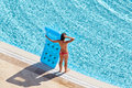 Young woman in red swimsuit stands on poolside holding blue inflatable mattress Stock Photos