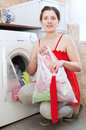 Young woman in red using bag for laundry at her home Stock Images