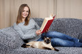 Young woman relaxing with a book and her cat on the couch Royalty Free Stock Photo