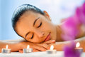Young woman relaxing in dimmed candle light after massage. Royalty Free Stock Photo