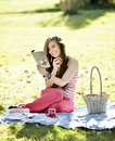 Young woman relaxing on the grass and eating apples women looking at book Royalty Free Stock Images