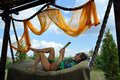 Young woman relaxing in hammock with tablet Royalty Free Stock Photo