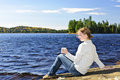Young woman relaxing at lake shore sitting with beverage on rock by beautiful in algonquin park canada Stock Images