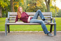 A young woman relaxing in a park with red hair her s on bench public Royalty Free Stock Photo