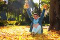 Young woman relaxing playing with leaves in autumn park happiness carefree pretty the throwing up the air arms raised up smiling Stock Photography