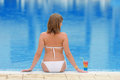 Young woman relaxing at the pool with cocktail Royalty Free Stock Photo