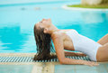 Young woman relaxing in poolside Stock Photo