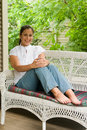 Young Woman Relaxing On Porch Stock Image