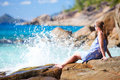 Young woman relaxing on rocky coast? Royalty Free Stock Images