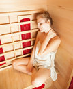 Young woman relaxing in a sauna and holding her neck color toned image Stock Photography