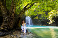 Young woman relaxing in water stream near waterfall Stock Images