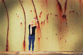 Young woman removes rust from wall Royalty Free Stock Photo
