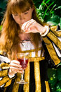 Young woman in renaissance dress poisoning wine Royalty Free Stock Photo