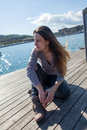 Young woman resting on harbor pier in barcelona is the beautiful sun the of the Royalty Free Stock Image