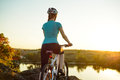 Young Woman Resting with Mountain Bike on Summer Rocky Trail and Looking at Beautiful Sunset. Travel, Sports and Adventure Concept Royalty Free Stock Photo