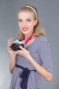 Young woman in retro clothes posing with old photo camera over grey Stock Photos