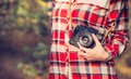 Young woman with retro photo camera and plaid shirt outdoor hipster lifestyle nature on background Royalty Free Stock Image