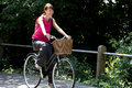A young woman riding a bicycle along a country road Stock Image