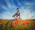 Young woman riding a bicycle on a blooming poppy meadow Royalty Free Stock Photo