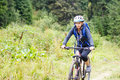 Young woman riding bicycle in mountain forest