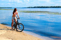 Young woman riding a bicycle slendre on bike on river beach Royalty Free Stock Photos