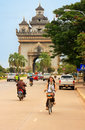 Young woman riding bike near Victory Gate Patuxai Royalty Free Stock Photo