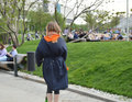 Young woman riding her scooter in the Park, the view from the back