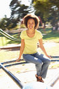 Young Woman Riding On Roundabout In Park Stock Photo