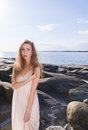 Young woman on rocky shore beautiful wearing white dress scandinavian and sea background Stock Photo