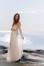 Young woman on rocky shore beautiful wearing white dress scandinavian and sea background Stock Images