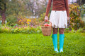 Young woman in rubber boots holding the straw basket with red apples at autumn time this image has attached release Stock Photos