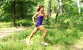 Young woman runner in a green forest Royalty Free Stock Photography