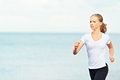 Young woman running on the beach on the coast of the sea morning jog Stock Image