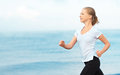 Young woman running on the beach on the coast of the sea morning jog Stock Photography
