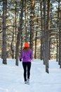 Young Woman Running in Beautiful Winter Forest at Sunny Frosty Day. Active Lifestyle Concept. Royalty Free Stock Photo