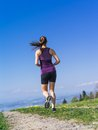 Young woman running on a country path photo of jogging and exercising lake in the distance Stock Photography