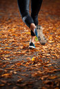 Young woman running in the early evening autumn leaves on road Stock Photography