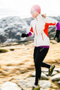 Young woman running in mountains on winter day Stock Photography