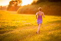 Young woman running outdoors on a lovely sunny summer evening shallow dof color toned image Royalty Free Stock Photos