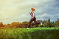 Young woman running side view of a on the grass Royalty Free Stock Photo