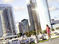 Young woman running by skyscrapers and harbour Royalty Free Stock Photo