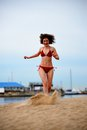 The young woman runs on a beach scattering feet sand Royalty Free Stock Photo