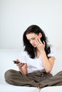 Young woman with sad expression looking at message on her cell phone Stock Photo