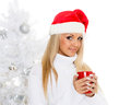 Young woman in santa claus cap with red cup stands near christmas tree on a white background Royalty Free Stock Images