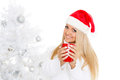 Young woman in santa claus cap with red cup stands near christmas tree on a white background Stock Photo