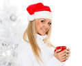 Young woman in santa claus cap with red cup stands near christmas tree on a white background Royalty Free Stock Image