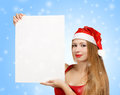 Young woman in santa claus hat with christmas card beautiful suit holding greeting or advertisement on blue background falling Stock Images